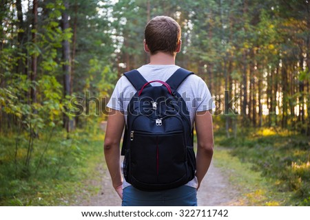 rear view of man with backpack hiking in forest - stock photo