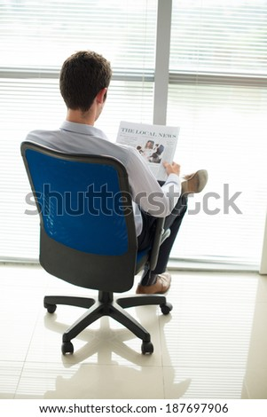 Rear view of manager reading newspaper in office - stock photo