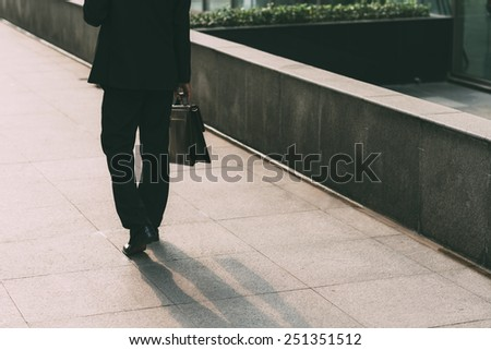 Rear view of manager walking down the street