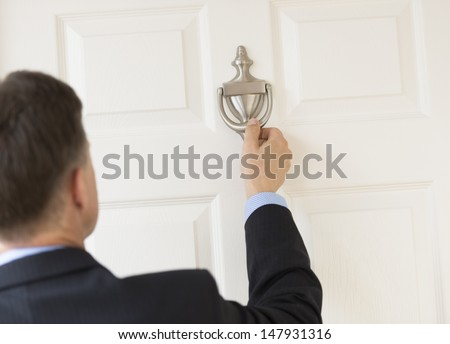 Rear view of mature businessman knocking door knocker - stock photo