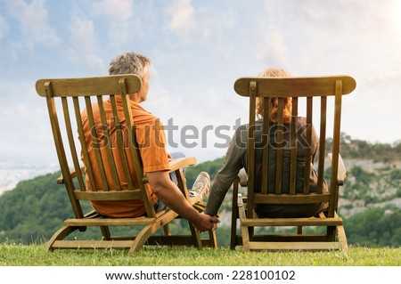 Rear View Of Mature Couple Sitting On Lounge Chair Holding Hands Conteplate the Future - stock photo