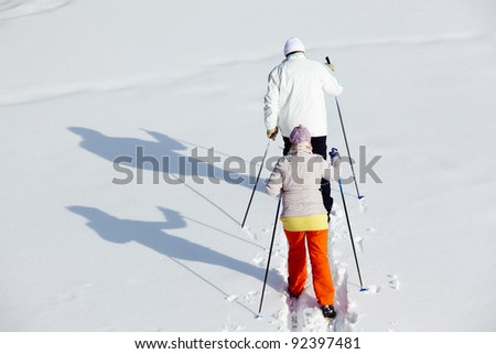 Rear view of mature couple skiing in winter park