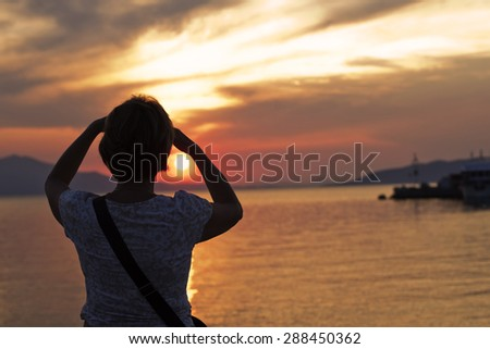 Rear  view  of mature woman enjoying sunset by the sea. - stock photo