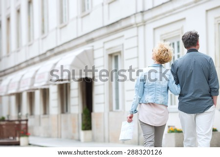 Rear view of middle-aged couple walking by building - stock photo