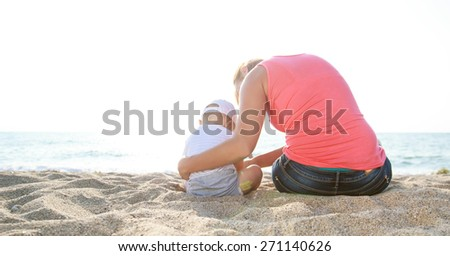Rear view of mother and baby boy sitting on the sandy beach and enjoy the summer day - stock photo