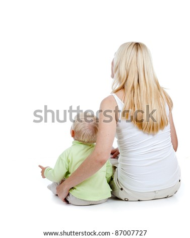 Rear view of mother and son seating together on floor in studio isolated - stock photo
