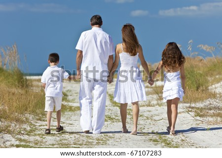 Rear view of mother, father and two children, son and daughter, walking holding hands in the sand of a sunny beach
