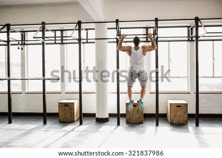 Rear view of muscular man doing pull ups at the gym - stock photo
