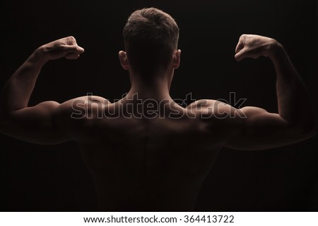 rear view of muscular man flexing arms and shoulders posing topless in dark studio background