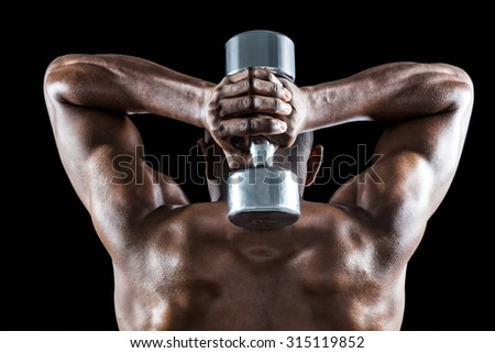 Rear view of muscular man lifting dumbbell behind head against black background