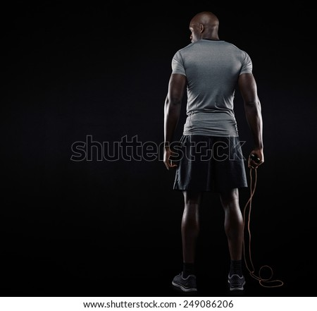 Rear view of muscular man standing with jumping rope on black background. Studio shot of fitness model holding skipping rope looking at copy space. - stock photo