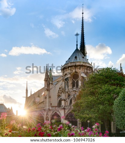 Rear view of Notre Dame De Paris cathedral at sunset with sun in the frame. Blue cloudy sky in background. Paris, France, Europe. - stock photo