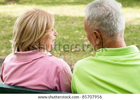 Rear view of old couple sitting and talking on park bench. - stock photo