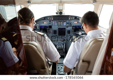 Rear view of pilot and copilot in cockpit of private jet - stock photo