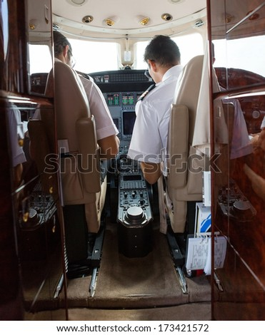 Rear view of pilot and copilot operating private jet - stock photo