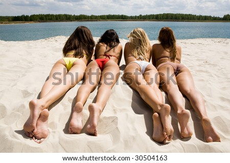 Rear view of pretty girls lying on sandy beach on hot summer day - stock photo