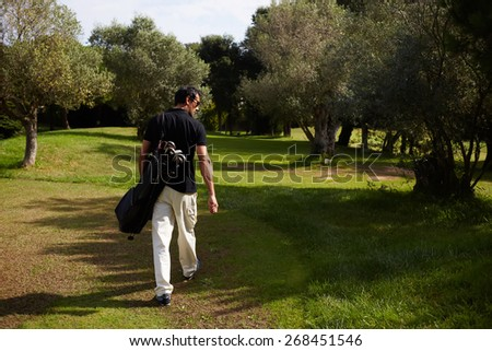 Rear view of professional male golfer walking to the next hole in golf course, good golf game at sunny summer day on the course - stock photo