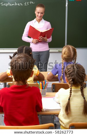 Rear view of pupils sitting at the lesson with teacher looking at them - stock photo