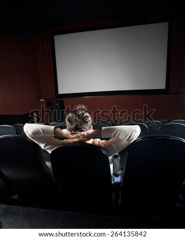 Rear view of relaxed man watching movie in cinema theater - stock photo