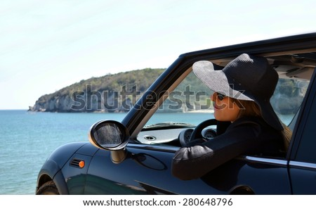 Rear view of relaxed woman on summer travel vacation to the coast leaning out car windows  towards the sea - stock photo
