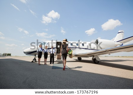 Rear view of rich woman walking towards private jet while pilot and stewardesses standing at airport terminal - stock photo
