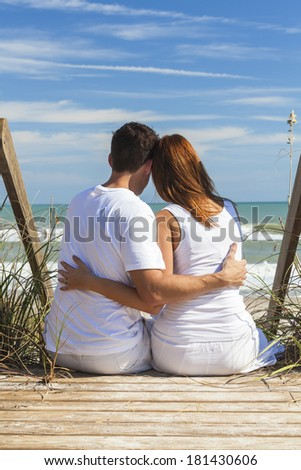 Rear view of romantic man & woman couple sitting on wooden steps overlooking a beach - stock photo