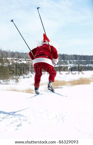 Rear view of Santa Claus jumping on skies - stock photo