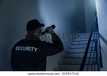 Rear view of security guard searching on stairway with flashlight in office building - stock photo