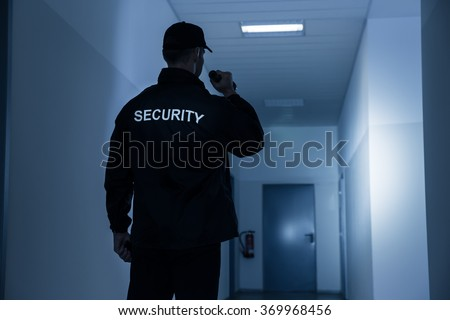 Rear view of security guard with flashlight in building corridor - stock photo