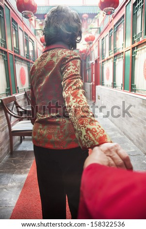 Rear view of senior couple holding hands - stock photo