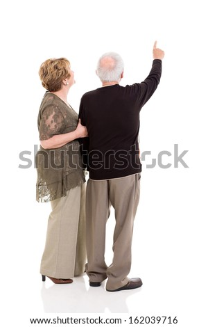 rear view of senior couple pointing at copy space on white background - stock photo