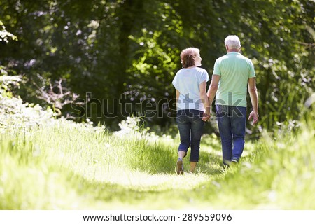 Rear View Of Senior Couple Walking In Summer Countryside - stock photo