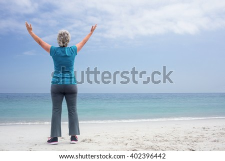 Rear view of senior woman standing on the beach with hands out stretched - stock photo