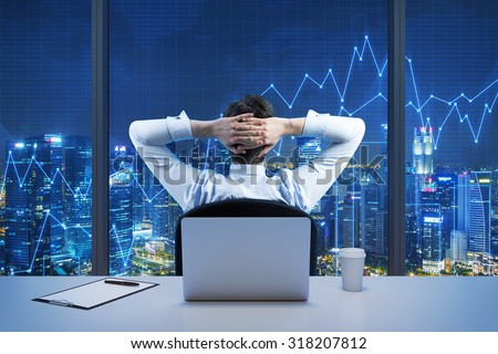 Rear view of sitting businessman who is looking at the city from the modern panoramic office. New York evening view. Crossed hands on the head. Financial charts are drawn over the panoramic windows. - stock photo