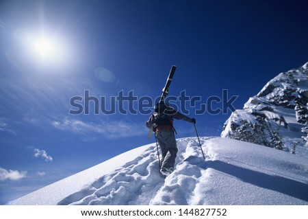 Rear view of skier hiking to mountain summit against sky - stock photo