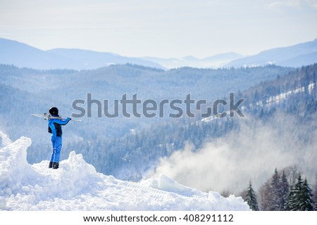 Rear view of skier standing on top of the mountain and enjoying the view on beautiful winter mountains on a sunny day. Skier is wearing blue ski suit and holding skis on her shoulder. Bukovel - stock photo
