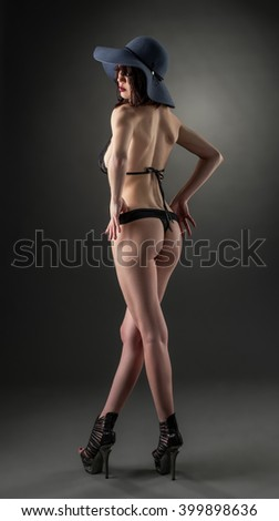 Rear view of slender model in lingerie and hat - stock photo