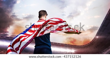 Rear view of sportsman holding an american flag against composite image of stadium against cloudy sky