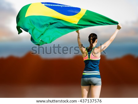 Rear view of sportswoman raising a brazilian flag against composite image of landscape