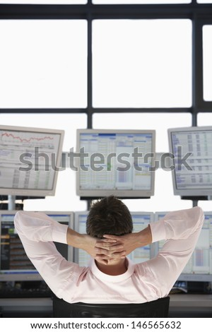 Rear view of stock trader with hands behind head watching multiple monitors - stock photo