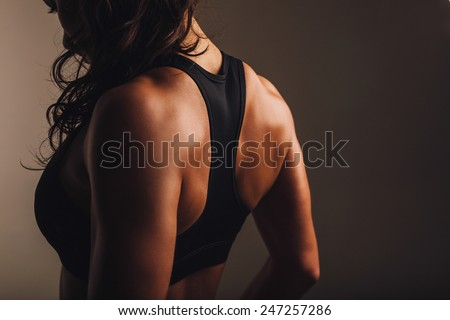 Rear view of strong young woman wearing sports bra. Muscular back of a woman in sportswear. - stock photo