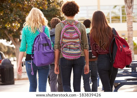 Rear View Of Students Walking To High School - stock photo