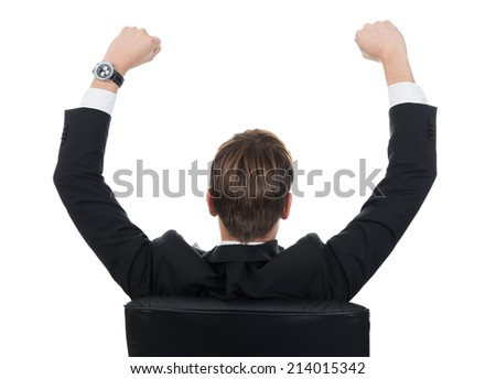 Rear view of successful businessman with arms raised sitting on chair on white background - stock photo