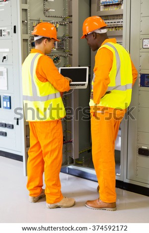 rear view of successful technicians using laptop in control room - stock photo