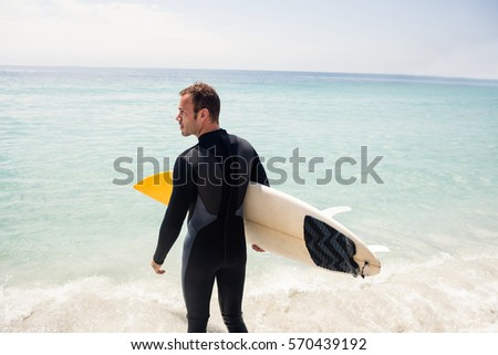 Rear view of surfer holding surfboard on beach on a sunny day