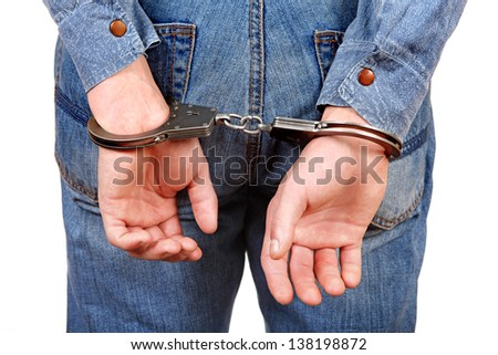 Rear view of the Man in Handcuffs on the White Background Closeup - stock photo