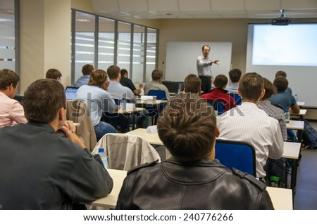 rear view of the people sitting in the class by the table and listening the presentation - stock photo