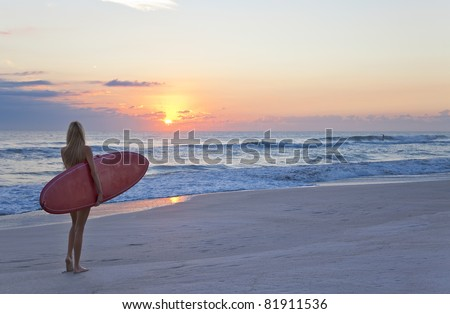 Rear view of three a young women surfer girl in bikinis with red surfboard on beach at sunset or sunrise - stock photo