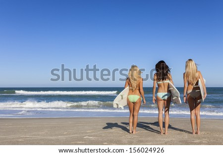 Rear view of three Beautiful young women surfer girls in bikinis with white surfbords at a beach - stock photo