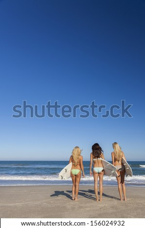Rear view of three Beautiful young women surfer girls in bikinis with white surfbords at a beach